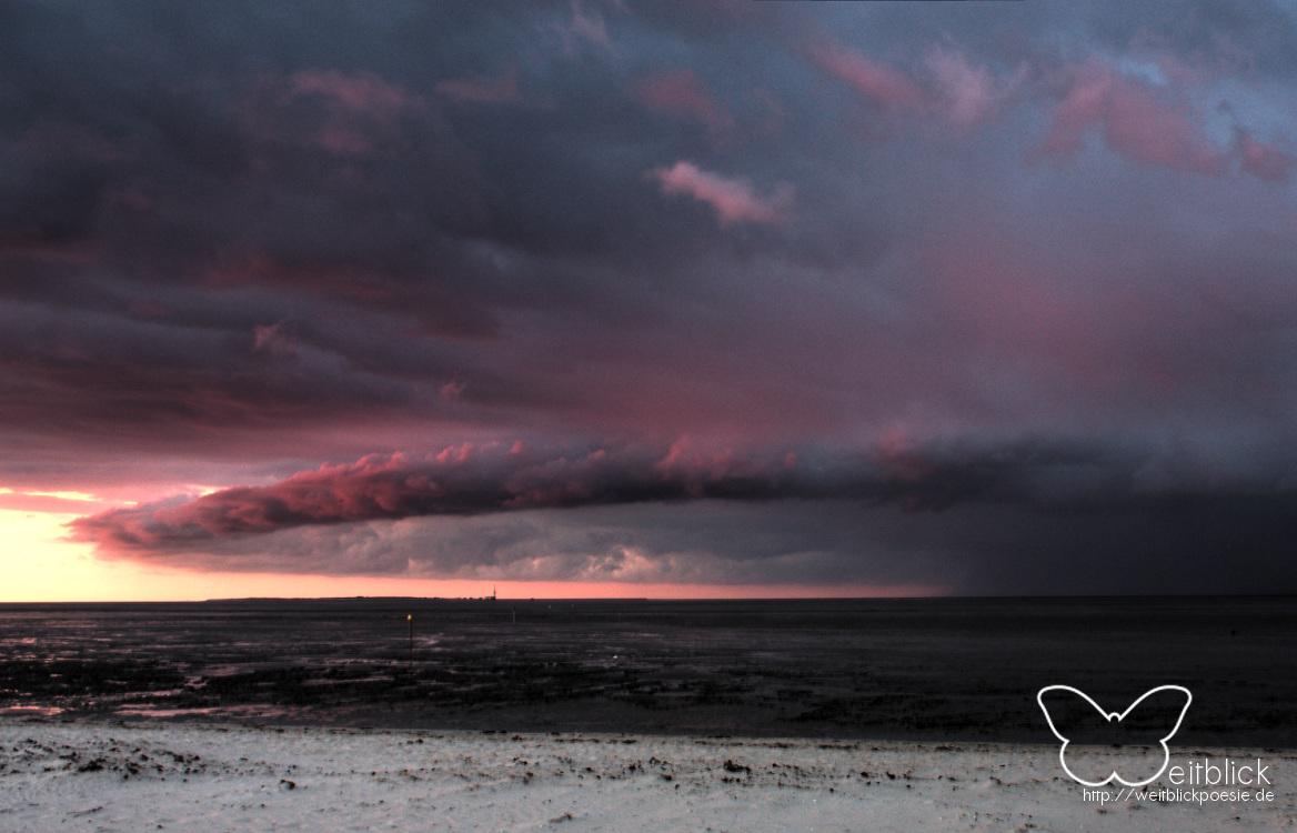Rechts vom Sonnenfall, weit über dem Watt, zog ein Sturm auf. Die dunklen Wolken annektierten das rote Abendlicht, um den Augen des Cerberus gleich Unheil anzukünden.  Eindrucksvolle Natur.